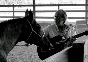 Pili singing and playing guitar for Utzie the horse